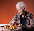 Senior woman tasting apple pie orange background Royalty Free Stock Photo