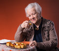 Senior woman tasting apple pie orange background Royalty Free Stock Images
