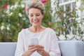 Senior woman texting message messagging with mobile phone while sitting on sofa in the garden older a phone with her new Royalty Free Stock Photos