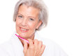 Senior woman with toothbrush in front of white background Royalty Free Stock Image