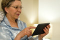 Senior woman using digital tablet in bed lying Stock Photo