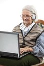 Senior woman using laptop computer over white holding isolated on background Stock Photos