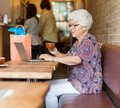 Senior woman using laptop while having coffee in side view of women cafeteria Royalty Free Stock Photos