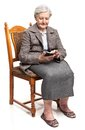 Senior woman using mobile phone sitting on chair while Royalty Free Stock Image