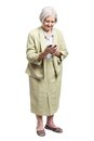 Senior woman using mobile phone while standing over white background Royalty Free Stock Photo