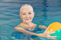Senior woman with water ball happy in swimming pool doing aqua fitness Stock Image