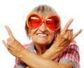 Senior woman wearing big sunglasses doing funky action isolated on white background Royalty Free Stock Photos