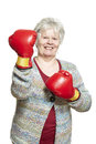 Senior woman wearing boxing gloves smiling white background Royalty Free Stock Image