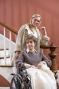 Senior woman in wheelchair at home with nurse Stock Images