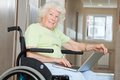 Senior woman in wheelchair using laptop happy sitting at hospital Royalty Free Stock Photo