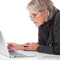 Senior woman working on a laptop profile portrait of an attractive leaning forwards to peer at something the screen Stock Images