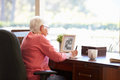 Senior woman writing memoirs in book at desk with hot drink Royalty Free Stock Photos