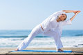 Senior woman yoga active exercise on beach Stock Photo