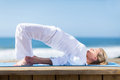 Senior woman yoga peaceful exercising outdoors on beach Royalty Free Stock Image