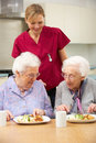 Senior women with carer enjoying meal at home Stock Photo