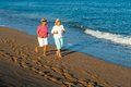 Senior women having early morning jog along sandy beach Royalty Free Stock Photos