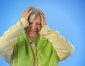 Senior worried woman with grey hairs against blue background Stock Photo