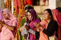 Senior and young hindu women in colourful sari perform puja at holy Sarovar lake,India