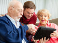 Seniors and adult son with tablet pc enjoys showing his parents how to use the new he gave them as a holiday gift Stock Photography