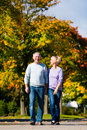 Seniors in autumn or fall walking hand in hand Stock Photography