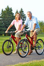Seniors couple biking Stock Images