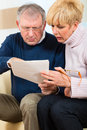 Seniors at home receiving a bad message two elderly people have received letter maybe it s reminder or bill but most likely it is Royalty Free Stock Image