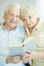 Seniors reading portrait of a candid senior couple book together Stock Photos