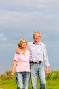 Seniors in summer walking hand in hand man and woman senior couple having a walk or outdoors the vineyard Stock Image