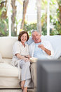 Seniors watching tv at home Royalty Free Stock Photos