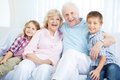 Seniors and youngsters portrait of happy grandparents with two grandchildren having rest at home Stock Photo
