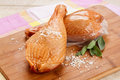 Sensational smoked leg of chicken seasoned with coarse salt on a plain wooden plate Stock Photo