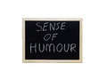 SENSE OF HUMOUR written with white chalk on blackboard