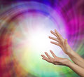 Sensing healing vortex pair of female hands reaching upwards into a vibrant energy field with plenty of copy space Royalty Free Stock Images