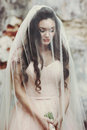 Sensual beautiful brunette bride holding a bouquet and hiding un Royalty Free Stock Photo