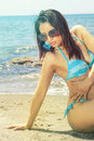 Sensual bikini woman on the sea beach with sunglasses