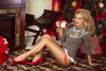 Sensual blonde girl in santa claus costume sexy beautiful woman posing at home christmas time Royalty Free Stock Images