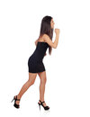 Sensual brunette girl with black dress running isolated on a white background Royalty Free Stock Image