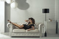 Sensual brunette lady lying at luxury couch white Royalty Free Stock Images