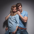 Sensual casual couple in a provocative pose against gray studio wall Stock Photography