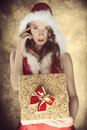 Sensual christmas female with cute present young long hair and sexy xmas dress wearing fur hood taking pretty gift box in the hand Royalty Free Stock Photos