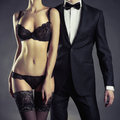 Sensual couple art photo of a young in lingerie and a tuxedo Stock Images