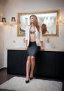 Sensual elegant woman in office outfit staying in front of a large mirror. Beautiful and sexy blonde young woman wearing sexy bra Royalty Free Stock Photo
