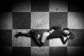 Sensual girl in corset and stockings on chess floor Royalty Free Stock Photo