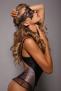 Sensual girl in lingerie corset with long blond hair with lace mask fashion studio photo of beautiful veil on face Royalty Free Stock Photography