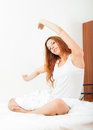 Sensual girl in shirt awaking on sheet white bed at home Royalty Free Stock Photography