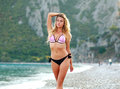 Sensual girl walking on summer sea beach in bikini Royalty Free Stock Photo