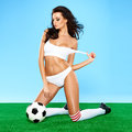 Sensual gorgeous brunette soccer player with a beautiful figure posing in white sports lingerie on her knees with a downcast Royalty Free Stock Photos