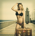 Sensual lady ready to travel in vintage color shot of sexy blonde with bikini sunglasses taking an old fashion suitcase Stock Photos
