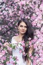 Sensual portrait of a spring woman, beautiful face, close up on blue eyes, female enjoying cherry blossom Royalty Free Stock Photo