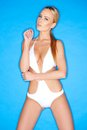 Sensual pretty blond woman in white swim wear posing looking at camera on gradient blue sky background Stock Images